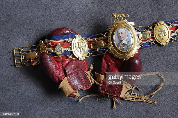 Henry Cooper's boxing gloves he wore during a bout against Cassius Clay in 1963 with his gold heavyweight Lonsdale belt for the heavyweight...