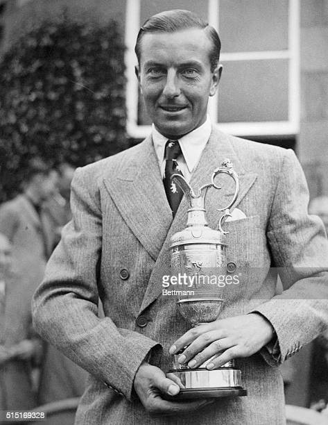 Henry Cotton is shown smiling as he holds the trophy for winning the British Open at Carnoustie Golf Course Carnoustie Scotland