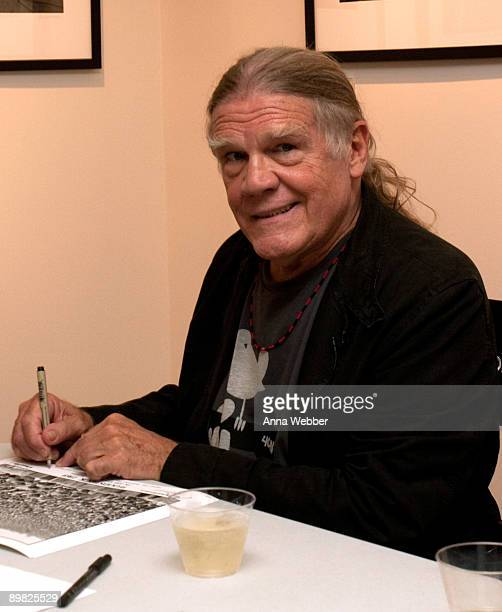 Henry Diltz signs posters at the Woodstock The 40th Anniversary in Pictures' Opening Reception for Artists at the Duncan Miller Gallery Los Angeles...