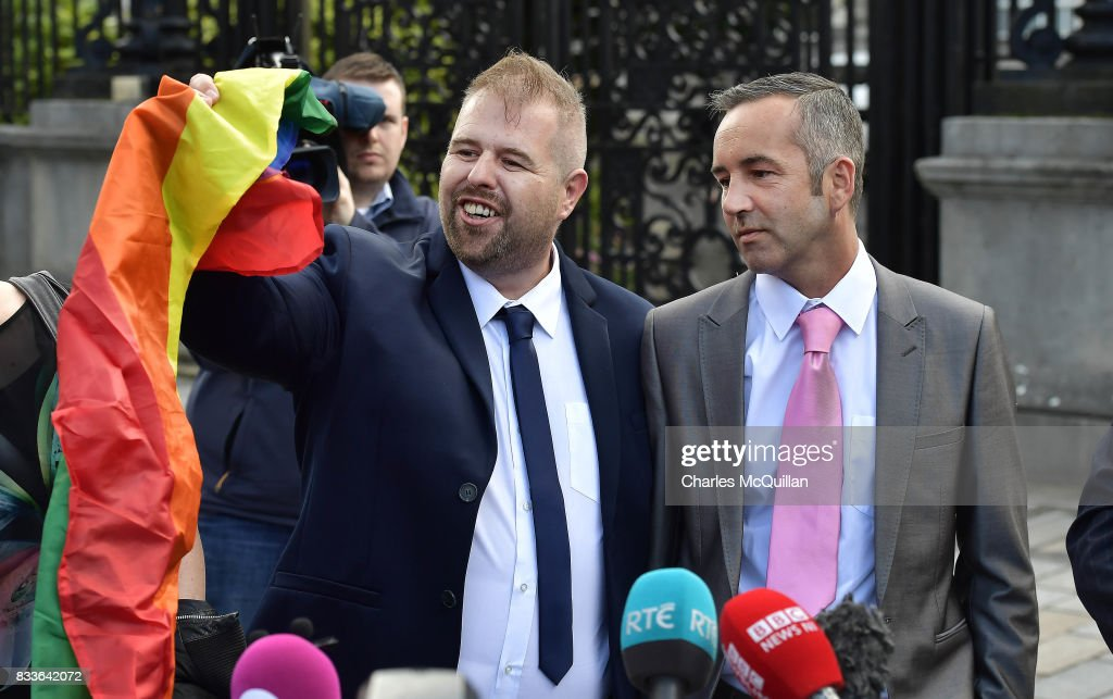 Henry Edmond Kane and Christopher Patrick Flanagan wave a rainbow flag at Belfast High Court as they speak to the media following the ruling on whether to allow same-sex marriage in Northern Ireland on August 17, 2017 in Belfast, Northern Ireland. The judge dismissed both cases before the court. Same-sex marriage is recognised in the rest of the United Kingdom but not in Northern Ireland were the largest political party, the DUP has blocked proposed legislation. Shannon Sickles and Grainne Close, the first women to have a civil partnership in the UK and Henry Edmond Kane and Christopher Patrick Flanagan were challenging the NI Assembly's repeated refusal to legislate for same sex marriage.