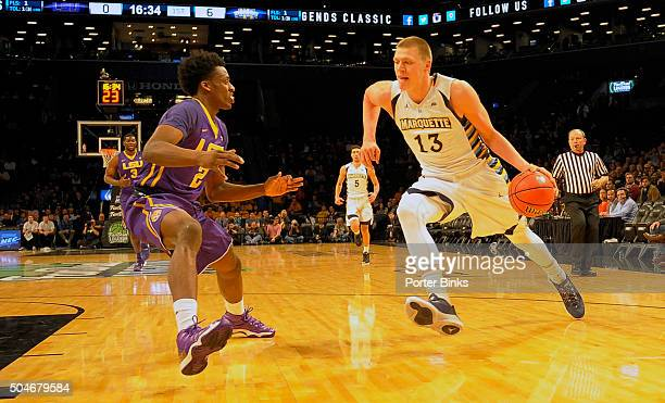 NEW YORK NY NOVEMBER 23 Henry Ellenson of the Marquette Golden Eagles drives against Antonio Blakeney of the LSU Tigers during the Legends Classic at...