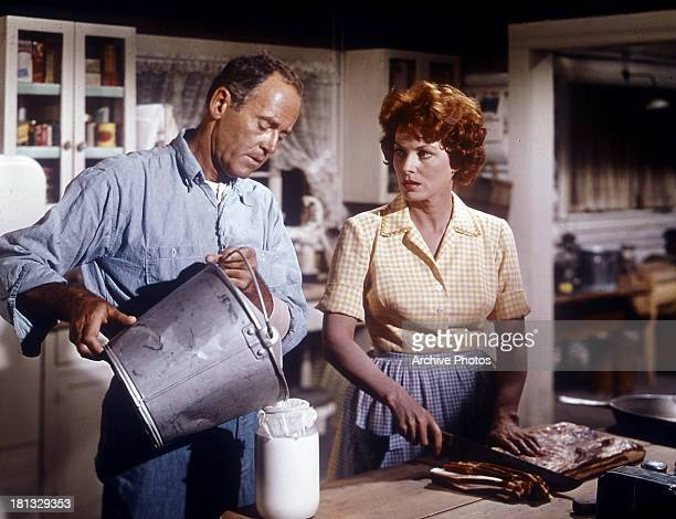 Henry Fonda helps Maureen O'Hara in the kitchen in a scene from the film 'Spencer's Mountain', 1963.