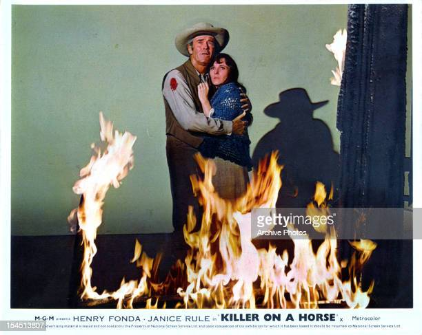Henry Fonda holding Janice Rule surrounded by fire in a scene from the film 'Welcome To Hard Times' 1967