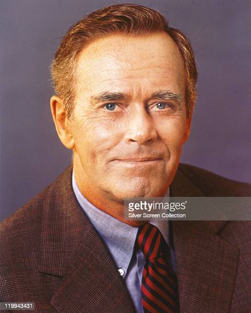 Henry Fonda US actor wearing a tweed jacket a blue shirt and a redandblack striped tie in a studio portrait against a lilac background circa 1960