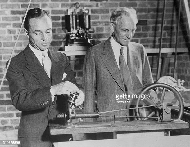Henry Ford and his son Edsel look over old machinery in the workshop where Henry Ford built the first Ford automobile. The workshop is preserved as...