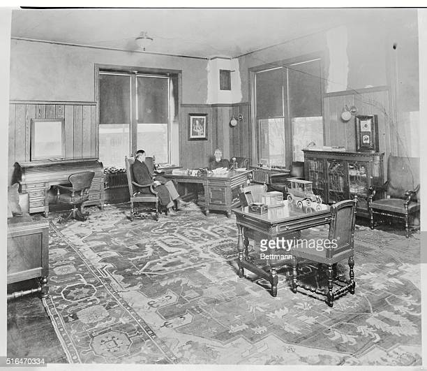 Henry Ford in his plush office in Highland Park Michigan The toy auto on front table is replica of a 1914 Model T landaulet