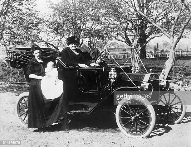 Henry Ford seated in a Model T on his Dearborn farm with his uncle Henry and possibly a greatniece
