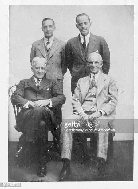 Henry Ford sits for a portrait with General Electric President Gerard Swope Standing behind Ford is WD Cameron and behind Swope is Edsel Ford