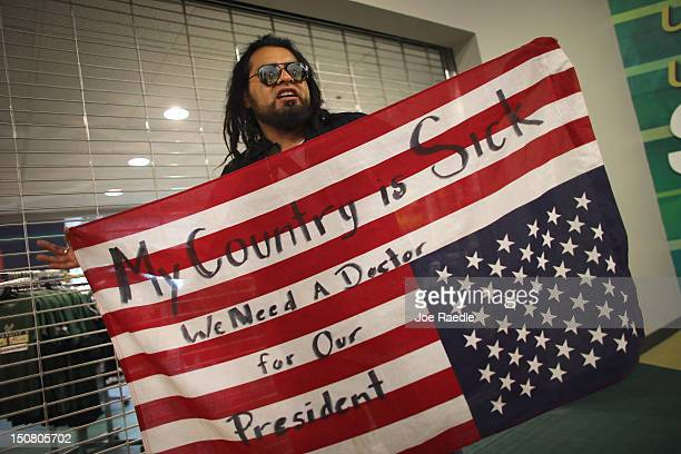 Henry Havoc holds an American flag where he wrote My Country is Sick We Need a Doctor for Our President' while waiting for former Republican...