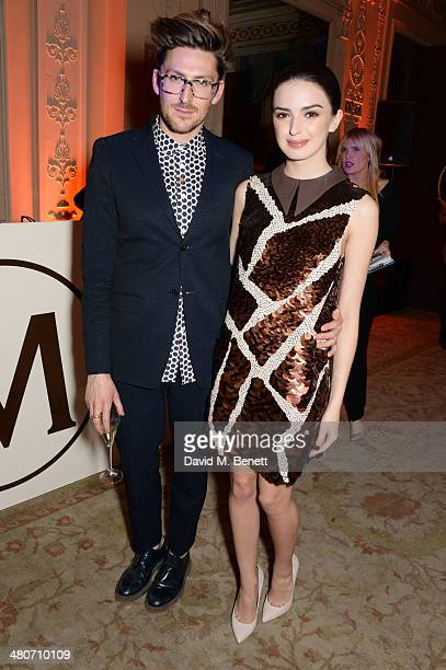 Henry Holland poses with a model wearing a dress he designed to celebrate 25 years of Magnum at Home House on March 26 2014 in London England