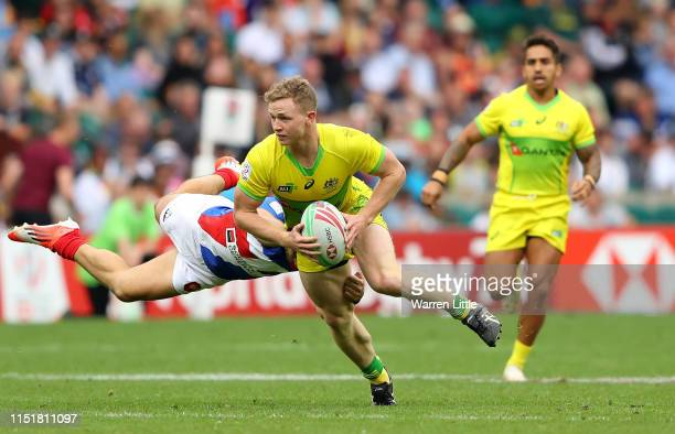 Henry Hutchison of Australia is tackled by Jean Pascal Barraque of France during the Cup Semi Final match on day two of the HSBC London Sevens at...