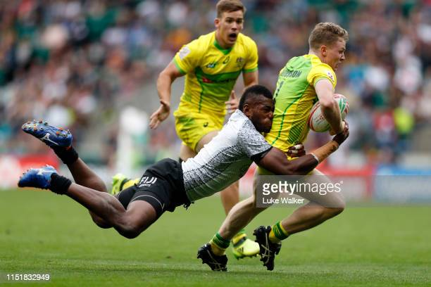 Henry Hutchison of Australia is tackled by Sevuloni Mocenacagi of Fiji during the cup final match between Australia and Fiji during the HSBC London...