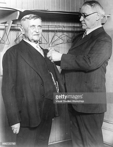 Henry J Killiles attorney for the Milwaukee railroad acting for the president pinning diamond medal on 'Soda Ash' Johnny Horan the road's and the...