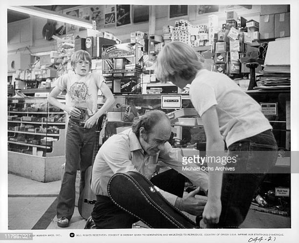 Henry Kendrick gesturing to Jodie Foster while Alfred Lutter III is tucking a wallet into his pant in a scene from the film 'Alice Doesn't Live Here...