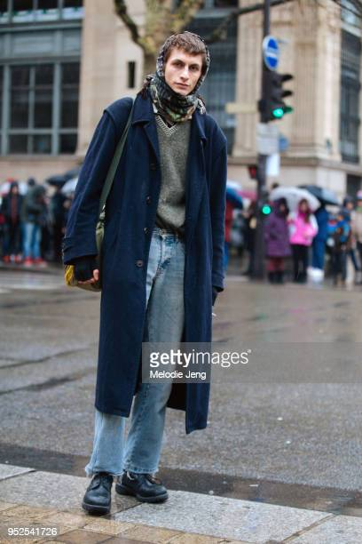 Henry Kitcher wears a scarf around his head a blue coat green sweater relaxed fit jeans and black boots on March 04 2018 in Paris France