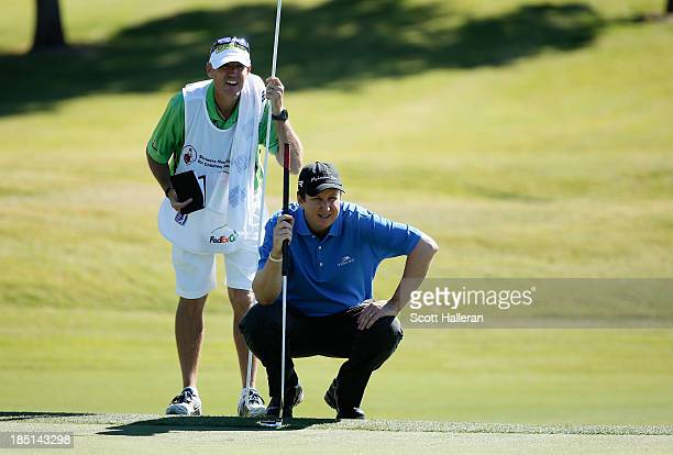 J Henry lines up his eagle putt with his caddie Don Donatello on the ninth green during the first round of the Shriners Hospitals for Children Open...