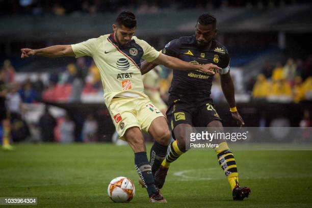 Henry Martin kicks the ball as he is marked by Gabriel Achiller of Moerlia during the 9th round match between America and Morelia as part of the...