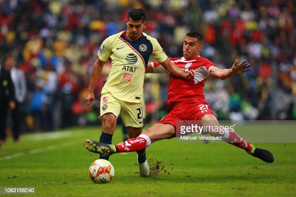 Henry Martin of America struggles for the ball against Enrique Triverio of Toluca during a 15th round match between Club America and Toluca as part...