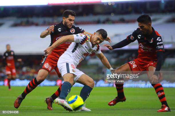 Henry Martin of America struggles for the ball with Hiram Muñoz and Juan Valenzuela of Tijuana during the 9th round match between America and Tijuana...
