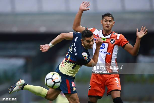 Henry Martin of America struggles for the ball with Javier Rivera of Tauro FC during the match between America and Tauro FC as part of the CONCACAF...