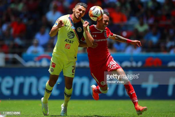 Henry Martin of America struggles for the ball with Rodrigo Salinas of Toluca during the 15th round match between Toluca and America as part of the...