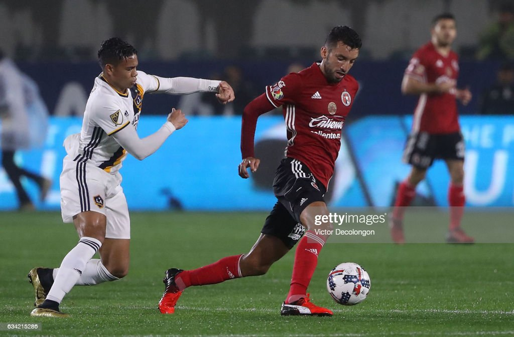 Henry Martin #11 of Club Tijuana plays the ball from Ariel Lassiter #15 of the Los Angeles Galaxy during their friendly match at StubHub Center on February 7, 2017 in Carson, California.