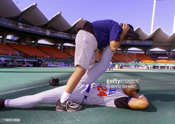 Henry Mercedes of the Dominican Republic's Tigres of Licey stretches 06 February as they warmed up for their game against Mexico's Aguilas de...