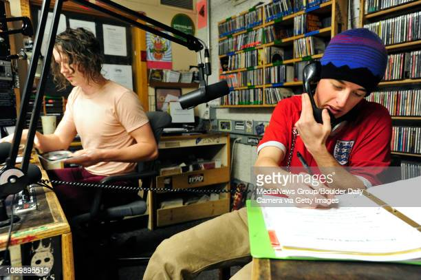 Henry Moffly, right, gives away concert tickets to a caller while Daniel Daenen runs the soundboard during the morning show at the University of...