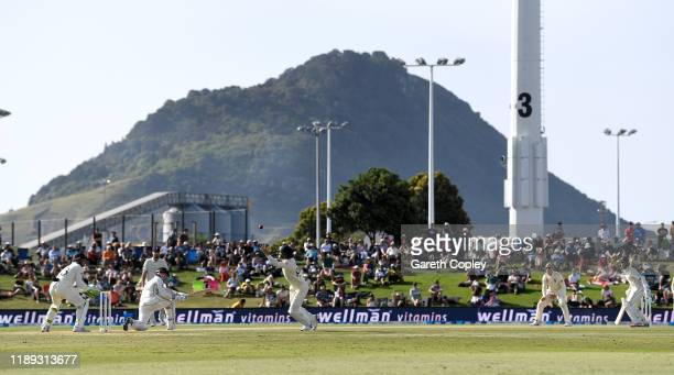 Henry Nicholls of New Zealand hits the ball past Ollie Pope of England during day two of the first Test match between New Zealand and England at Bay...