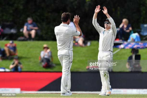 Henry Nicholls of New Zealand is congratulated by Colin de Grandhomme of New Zealand after taking a catch to dismiss Dawid Malan of England during...