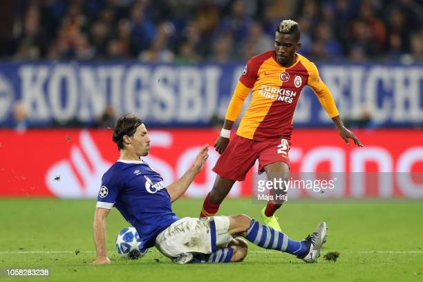 Henry Onyekuru of Galatasaray is challanged by Benjamin Stambouli of FC Shalke 04 during the Group D match of the UEFA Champions League between FC...