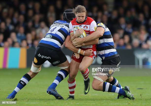 Henry Purdy of Gloucester is held by Luke Charteris and Charlie Ewels during the Aviva Premiership match between Bath Rugby and Gloucester Rugby at...