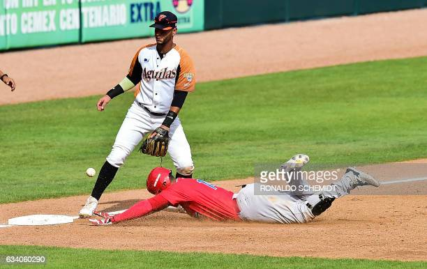 Henry Ramos of Criollos de Caguas of Puerto Rico slides safe in third base during the Caribbean Baseball Series match against Aguilas del Zulia of...
