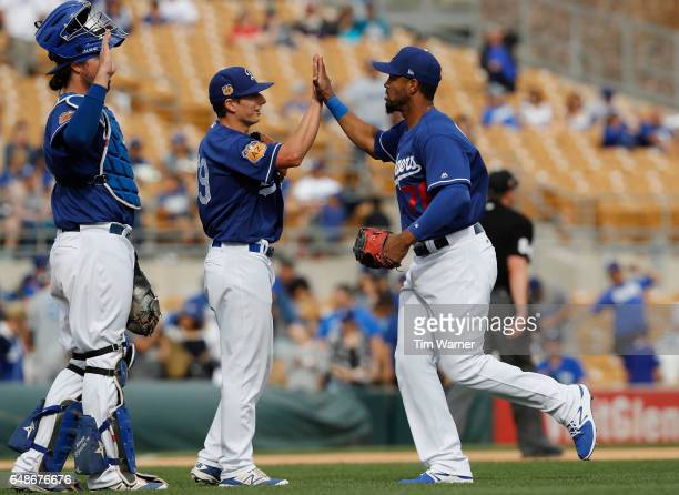 Henry Ramos of the Los Angeles Dodgers celebrates with Andrew Istler and Jack Murphy after the spring training game against the Seattle Mariners at...