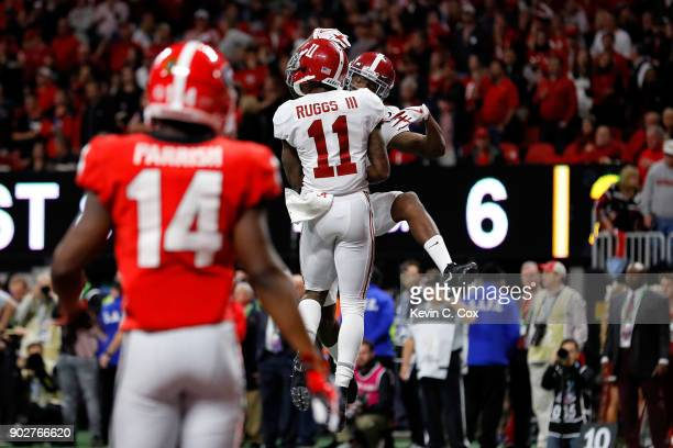 Henry Ruggs III of the Alabama Crimson Tide celebrates a six yard touchdown catch with Robert Foster during the third quarter against the Georgia...
