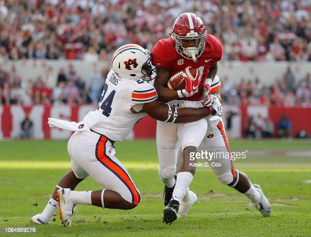 Henry Ruggs III of the Alabama Crimson Tide is tackled by Daniel Thomas and Deshaun Davis of the Auburn Tigers at Bryant-Denny Stadium on November...