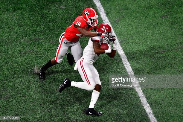 Henry Ruggs III of the Alabama Crimson Tide is tackled by JR Reed of the Georgia Bulldogs after a catch during the third quarter in the CFP National...