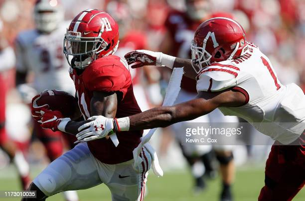 Henry Ruggs III of the Alabama Crimson Tide pulls in this reception against Ray Buford Jr #1 of the New Mexico State Aggies at BryantDenny Stadium on...