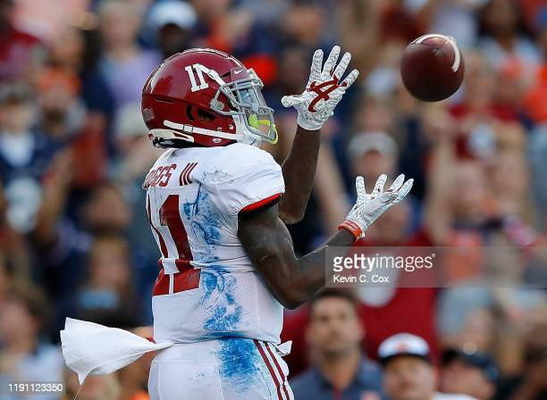 Henry Ruggs III of the Alabama Crimson Tide pulls in this touchdown reception against the Auburn Tigers in the first half at Jordan Hare Stadium on...