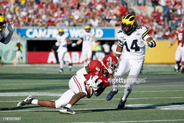 Henry Ruggs III of the Alabama Crimson Tide reaches but is not able to catch a pass against the Michigan Wolverines in the third quarter of the Vrbo...