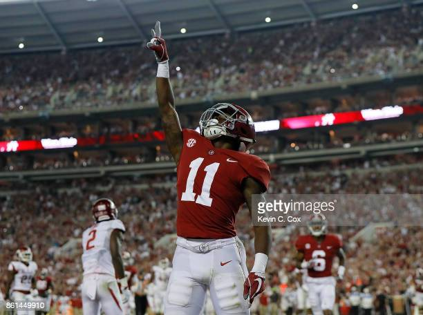 Henry Ruggs III of the Alabama Crimson Tide reacts after pulling in a touchdown reception against the Arkansas Razorbacks at BryantDenny Stadium on...