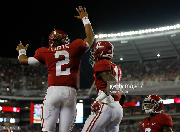 Henry Ruggs III of the Alabama Crimson Tide reacts after pulling in a touchdown reception against the Arkansas Razorbacks with Jalen Hurts at...