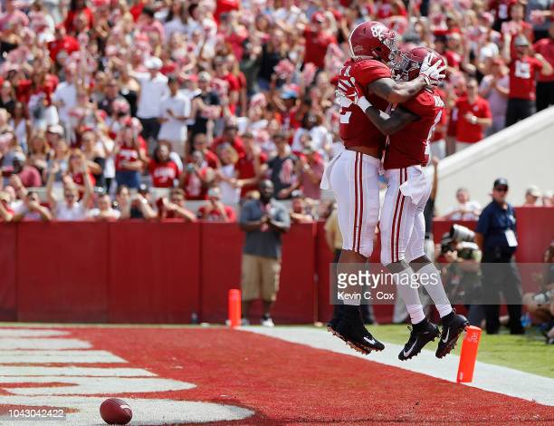 Henry Ruggs III of the Alabama Crimson Tide reacts with Irv Smith Jr #82 after scoring a touchdown against the Louisiana Ragin Cajuns at BryantDenny...
