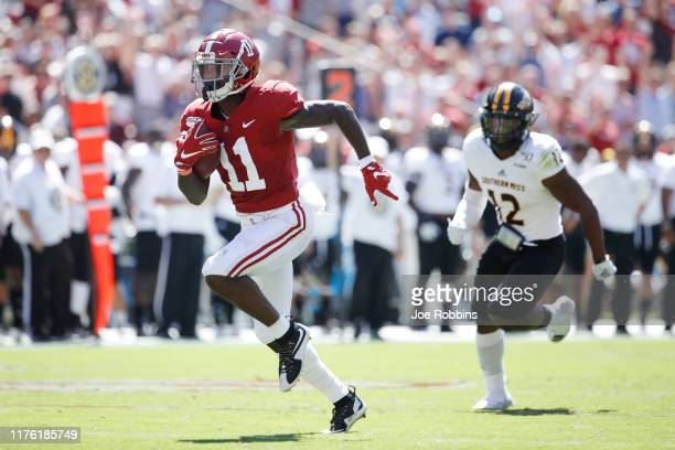 Henry Ruggs III of the Alabama Crimson Tide runs for a 45-yard touchdown in the first quarter after catching a pass behind D.Q. Thomas of the...