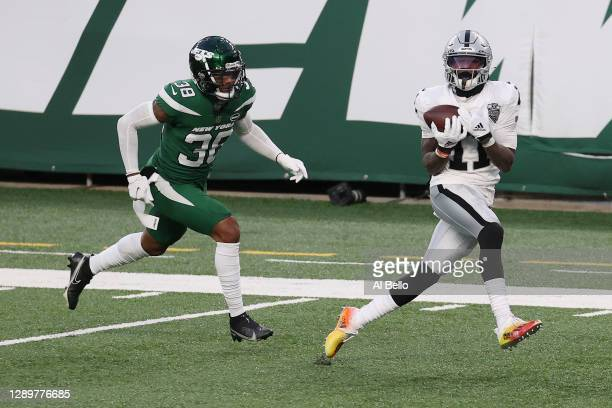 Henry Ruggs III of the Las Vegas Raiders catches a touchdown pass to win the game as Lamar Jackson of the New York Jets gives chase during the second...