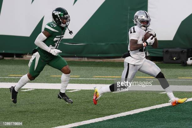 Henry Ruggs III of the Las Vegas Raiders scores a touchdown to win the game as Lamar Jackson of the New York Jets gives chase during the second half...