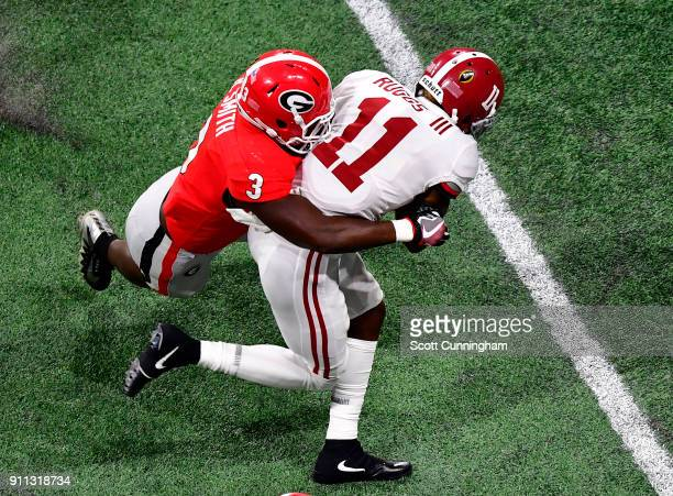 Henry Ruggs of the Alabama Crimson Tide is tackled by Roquan Smith of the Georgia Bulldogs in the CFP National Championship presented by ATT at...