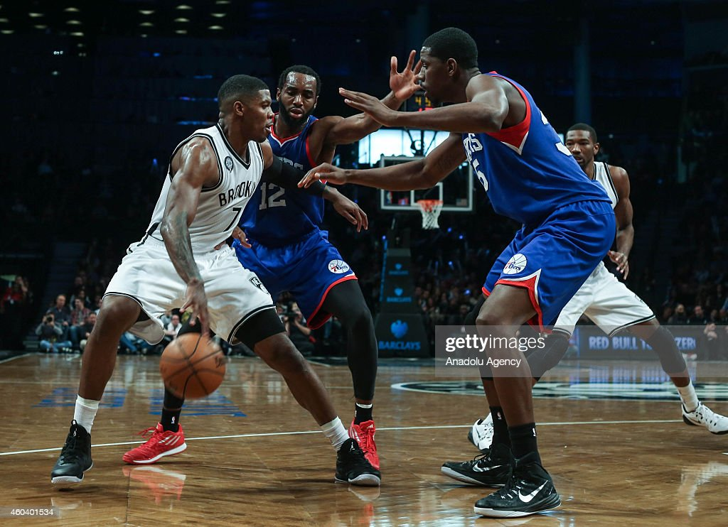 Henry Sims (R) and Luc Mbah a Moute #12 of Philadelphia 76ers vie with Joe Johnson #7 of Brooklyn Nets during a basketball game at the Barclays Center on December 12, 2014 in the Brooklyn borough of New York, NY.