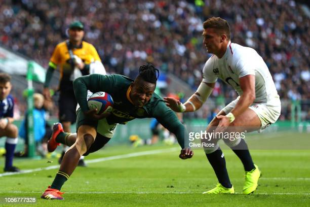 Henry Slade of England attempts to tackle Sibusiso Nkosi of South Africa as he scores his team's first try during the Quilter International match...