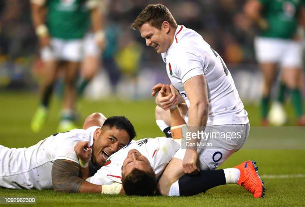 Henry Slade of England celebrates with teammates Manu Tuilagi of England and Chris Ashton of England after scoring their side's fourth try during the...